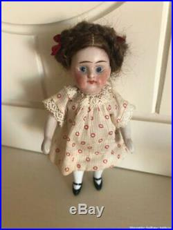 Antique tiny bisque doll with clothes in the basket